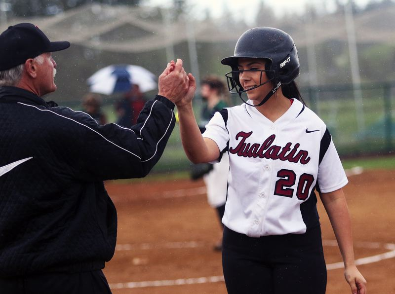 DAN BROOD - Tualatin High School junior Zoe Olivera (right) gets a high five from Timberwolf assist coach Bill Wilson after getting a hit against Tigard in a game played this past spring.
