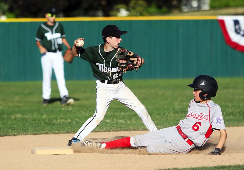 DAN BROOD - Tigard shortstop Owen Magnusen (left) looks to make a throw to first base in an attempt to turn a double play in Saturday's District 4 tournament game.