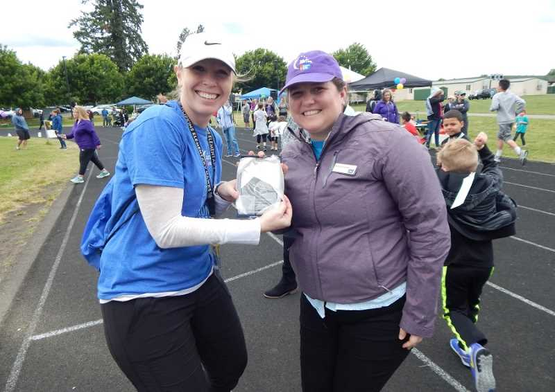 SHERWOOD GAZETTE PHOTO: BARBARA SHERMAN - Rachel Murphy (right) with the American Cancer Society hands Hopkins teacher Marika Conrad an engraved plaque commemorating the school's 10 years of raising funds for the organization.