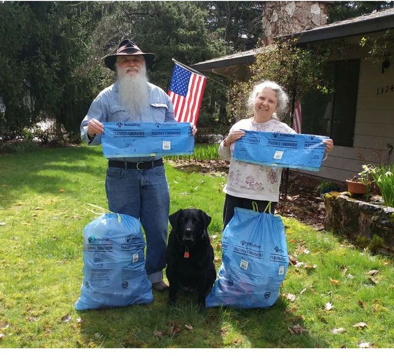 SUBMITTED PHOTO  - Oregon City Parks Foundation board members William and Joyce Gifford demonstrate how easy it is to donate cans and bottles to the nonprofit using specially marked blue bags.