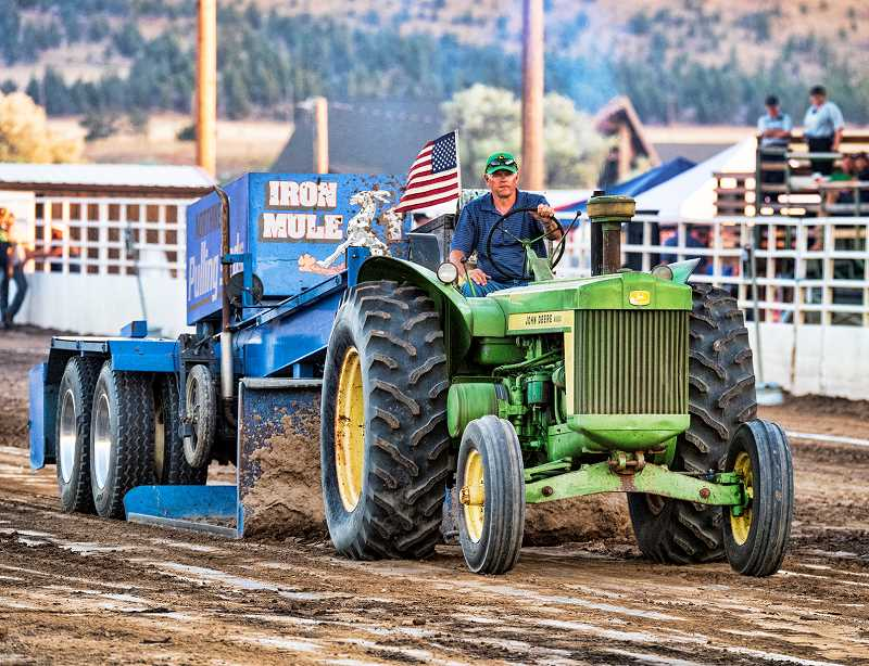 LON AUSTIN/CENTRAL OREGONIAN - Doug Smith makes a pull with a 1957 John Deer tractor. Smith won the stock tractor division at the event with a pull of 308.51 feet. The second annual truck and tractor pull at the Crook County Fairgrounds saw more than 400 spectators each day of the two-day event as some of the top tractors and trucks in the Northwest competed at the event.