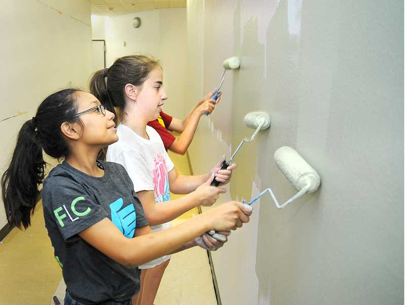 SETH GORDON - (From left to right) Incoming sixth grade students Alyssa Resendiz, Evie Palmer and Jordan DeBolt paint a hallway at Mountain View Middle School. Over the past 17 days, volunteer parents, students and staff have been repainting the walls in green or blue, the school's colors.