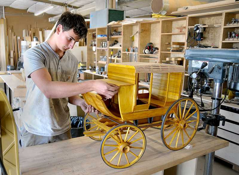 SETH GORDON - ANewberg High School and Anvil Academy student Roehben Sarkisian attaches a chain to his quarter-scale model stagecoach which was named a finalist in the Association of Woodworking & Furnishings Suppliers Fresh Wood student woodworking contest.
