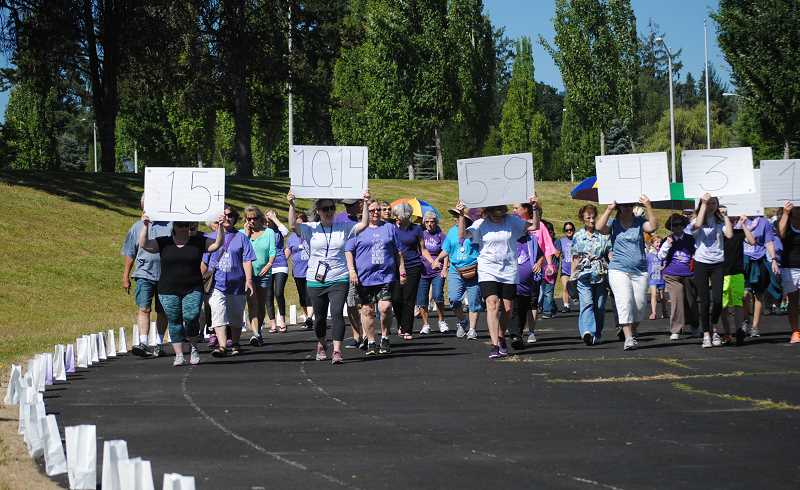 NEWS-TIMES PHOTOS: EMILY GOODYKOONTZ - Cancer survivors hold up cards denoting the number of years they have survived their cancer diagnosis during the survivors lap the the Relay for Life of Western Washington County on Saturday, July 8.