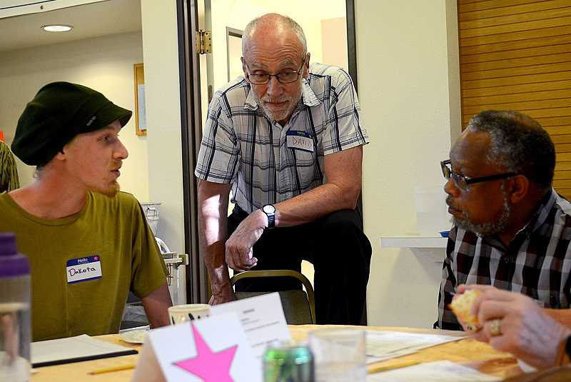 REVIEW PHOTO: VERN UYETAKE - Dakota Gonzalez (from left), David Dunning and Bruce Poinsette chat during a community gathering Monday evening that was billed as a response to racism in Lake Oswego. More than 50 local residents attended.