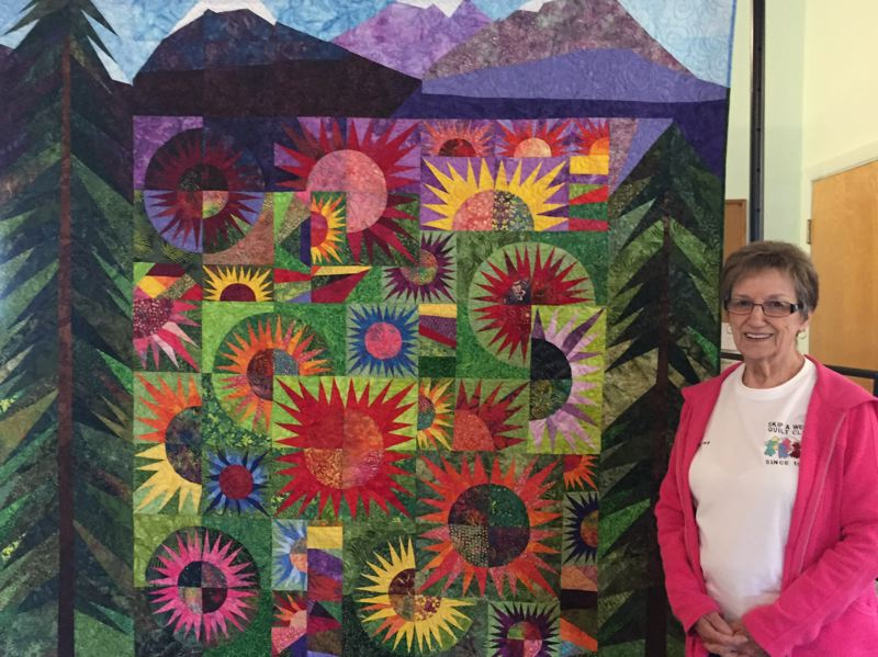 ESTACADA NEWS PHOTO: EMILY LINDSTRAND - Sharon Young, the featured quilter at this years Garfield Skip-A-Week Club, shows one of the quilts shes made that will be on display during the show, which is scheduled for Friday, June 21, and Saturday, July 22.