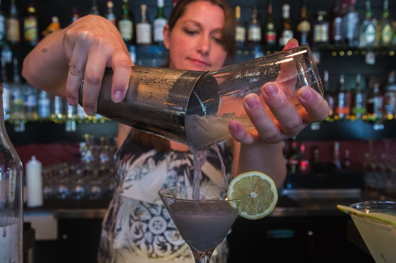 OUTLOOK PHOTO: JOSH KULLA - Elizabeth Baker, managing bartender at Troutini in downtown Troutdale, puts together a Portland Sunshine martini.
