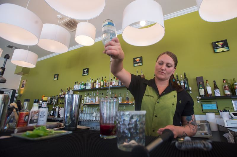 OUTLOOK PHOTO: JOSH KULLA - Happy Hour bartender Randee Hyneman puts together a blackberry basil martini, one of the downtown Gresham bar's specialities.