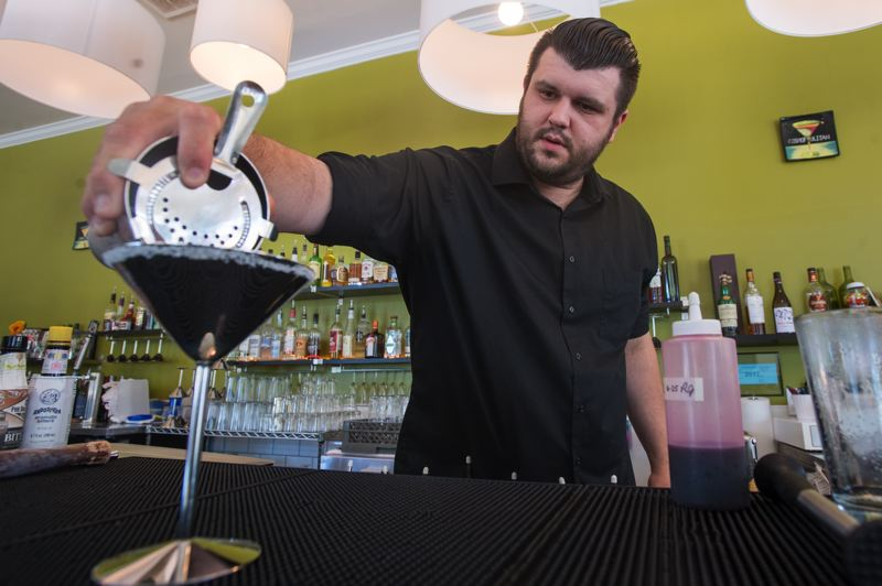 OUTLOOK PHOTO: JOSH KULLA - Bartender Randy Jeffers likes to prepare the Happy Hibiscus, Happy Hour's most popular cocktail. Here, he pours the final product into the establishment's distinctive stainless steel glasses.