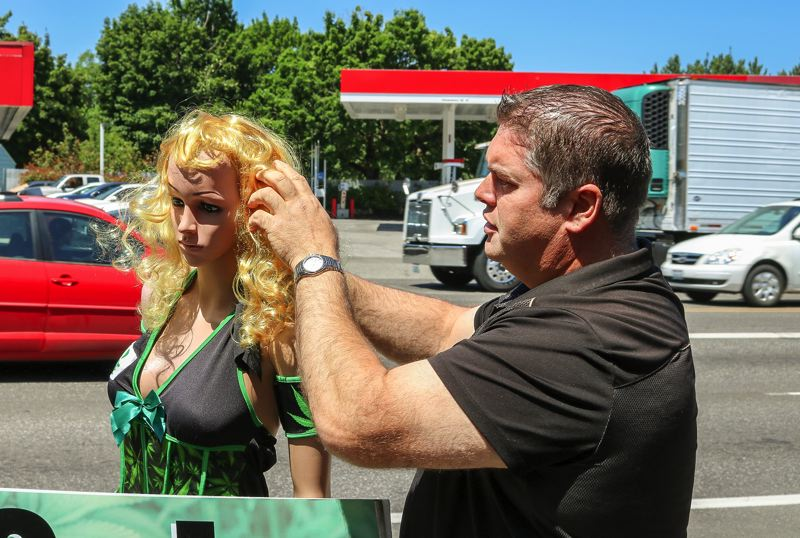 OUTLOOK PHOTO: ZANE SPARLING - Aaron Michelsen adjusts a street mannequin he uses to promote his marijuana business in Wood Village.