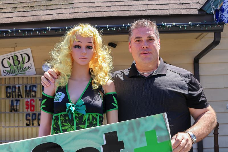 OUTLOOK PHOTO: ZANE SPARLING - Aaron Michelsen stands next to a marijuana mannequin he was fined $1,000 for outside his Wood Village dispensary in July.