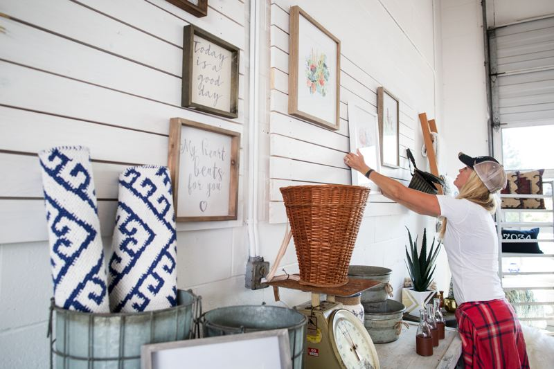 TIMES PHOTO: JAIME VALDEZ - Angela Dickson, owner of The Oilery by The Little Door, hangs photos at her new store in Tualatin.