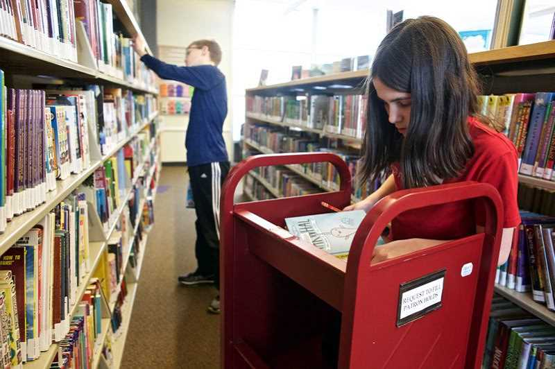 TIMES FILE PHOTO: JAIME VALDEZ - Julia Martin, 11, foreground, and her older brother, Kennin, 14, find books on order at the Tigard Public Library.