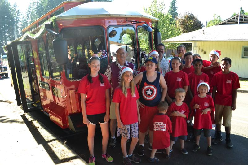 POST PHOTO: BRITTANY ALLEN - The Sandy City Council and staff members from the Sandy Transit Department pose in front of the brand new Sandy shopping shuttle before the Sandy Mountain Festival parade on Thursday, July 6.