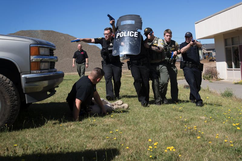 TIMES PHOTO: JAIME VALDEZ - Officers from city police agencies and sheriff's offices learn how to carry a 'wounded' officer, while protecting themselves, during a day of training at the soon-to-be demolished Hazeldale Elementary School.