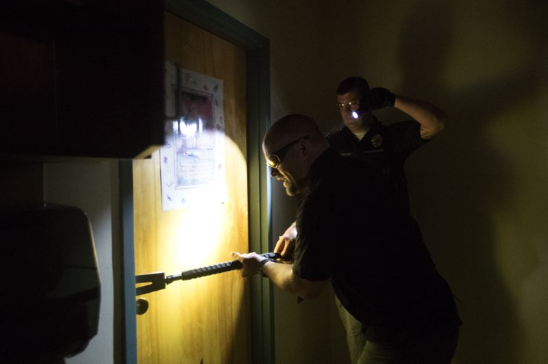 TIMES PHOTO: JAIME VALDEZ - Cpl. Jeremy Braun, Washington County Sheriff's Office, shows the right way to use a halligan bar — an all-purpose hatchet/crow bar/ice pick — to bust open a door.