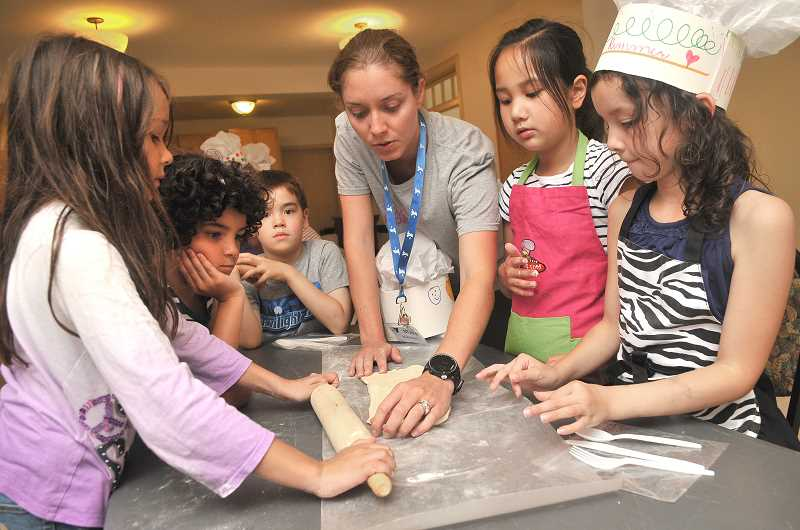 TIDINGS PHOTO: VERN UYETAKE - YMCA's Kimberly Hillas, middle, leads kids through a baking activity Thursday, July 6 at the Sunset Fire Hall.
