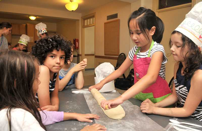 TIDINGS PHOTO: VERN UYETAKE - Kids roll out dough during a YMCA-sponsored baking camp last week.