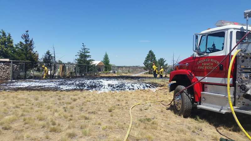 SUBMITTED PHOTO - On Friday, Crooked River Ranch Fire and Rescue personnel mop up a small fire on Peninsula Drive, which was caused by exhaust from a weed-eater, which ignited dry grass at Crooked River Ranch.