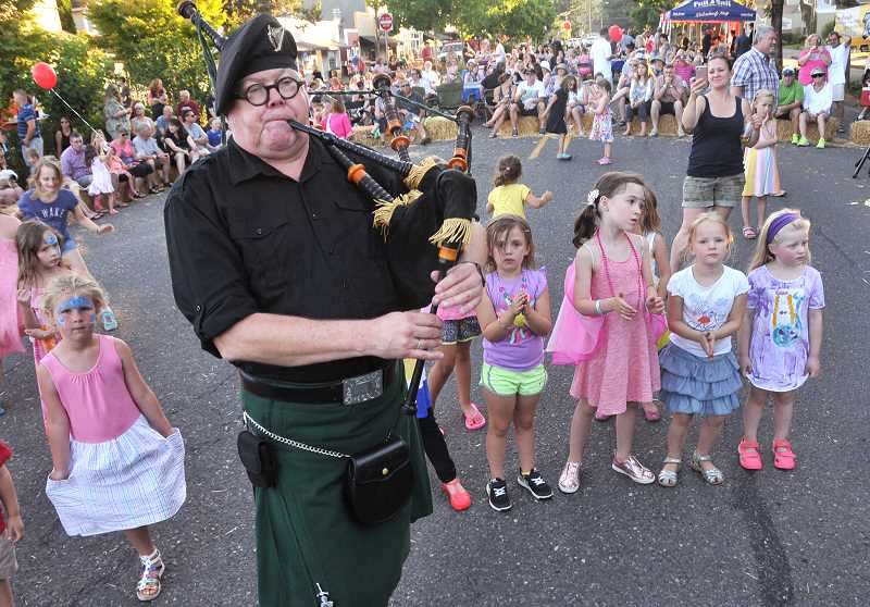 Tim Birr of the Tualitan Valley Fire and Rescue pipe and drum group  delights kids with his bagpipes during the opening ceremony.