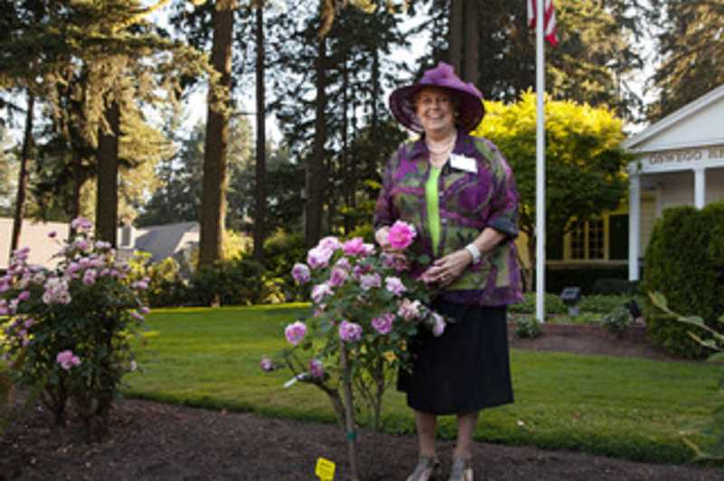 SUBMITTED PHOTO  - Nancy Dunis stands by her favorite rose, the General Pershing, in the historic rose garden at Oswego Heritage House. All are welcome to visit the garden.