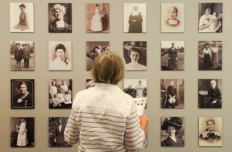 REVIEW PHOTO: VERN UYETAKE - Judy Dauble takes a closer look at 'Creating Community: Oswego Women,' a collection of historical photos and documents now on display at the Oswego Heritage House in Lake Oswego.