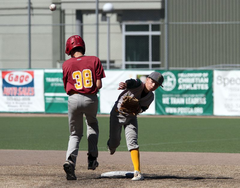 TIDINGS PHOTO: MILES VANCE - West Linn shortstop Cam Ortiz tries to turn a double play during his team's 13-1 win over The Dalles in the championship game of the 13U Babe Ruth state championship game on Saturday at West Linn High School.