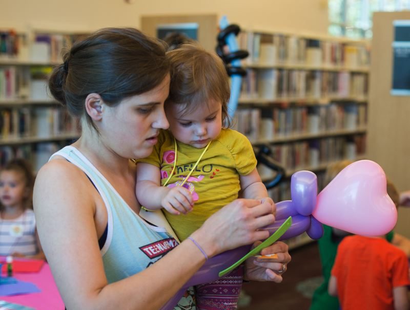 OUTLOOK PHOTO: JOSH KULLA - Jamie and Winnie Daily put together a balloon animal Wednesday during a game day to celebrate the opening of the Gresham Library's summer lunch program.