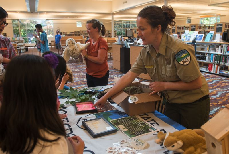 OUTLOOK PHOTO: JOSH KULLA - Oregon State Parks staffer Sophie Contreras shows children at the Gresham Library Wednesday how to identify certain animals in the wild.