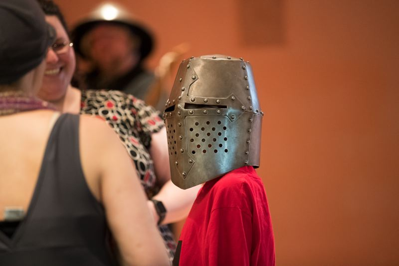 TIMES PHOTO: JAIME VALDEZ - A young Tigard Library patron tries on a replica medieval helmet during a program by the Knights of Veritas, a group of educators.