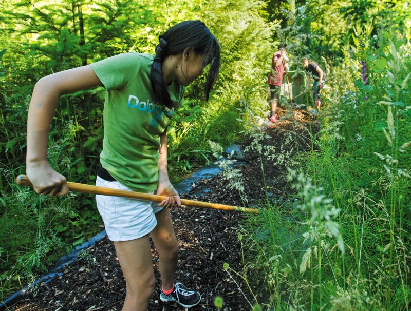 PAMPLIN MEDIA GROUP: JOSH KULLA  - West Orient student Gracie Casper works her rake as she helps clean up the schools nature trail during a recent spring morning.