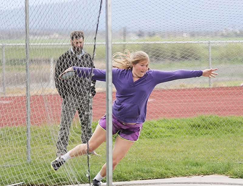 PIONEER FILE PHOTO - Above, Mike Dove (left) looks on as then-freshman Catylynn Duff works on her discus throw during practice. Dove resigned as the Bulldogs' head track and field coach and a high school science teacher at Culver following the 2017 season in which Duff won a state title in the discus, and two other Bulldogs took second place at state.