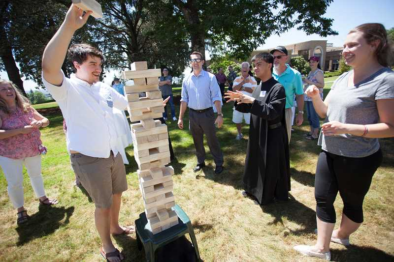 COURTESY PHOTO: MOUNT ANGEL ABBEY - Brother Matthew, OSB (center), a monk of Mount Angel Abbey, engages with Abbey guests in a lawn game version of Jenga.