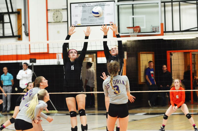 SPOTLIGHT PHOTO: JAKE MCNEAL - Indians seniors Kristina Barnes (middle blocker, 11) and Hannah Galey (outside hitter, 5) leap to contest a shot against Astoria last fall.