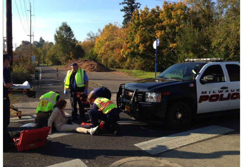 PHOTO BY: BRYAN MORRIS/CCSO - Clackamas Fire paramedics attend to Gillian Hibbs after she was hit in the Springwater Trails crossing of Johnson Creek Boulevard by a Milwaukie police officer.