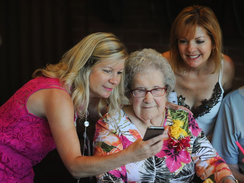 OUTLOOK PHOTO: JOSH KULLA - Granddaughters Lori Cooper and Lisa Plancich look on as their grandmother, Marguerite Inman, checks out a photo during her 100th birthday celebration on Friday, July 14, at Heidi's Restaurant in Gresham. The gathering brought together 50 or more family members.