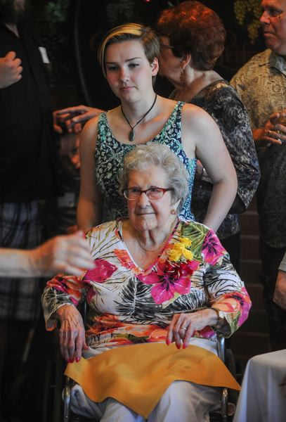 OUTLOOK PHOTO: JOSH KULLA - Great granddaughter Jaimia Plancich wheels Marguerite Inman to the main table for her birthday speech.