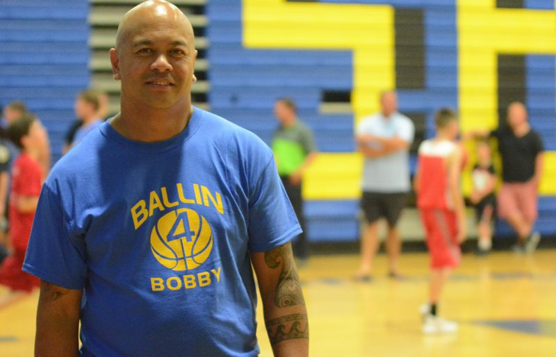 OUTLOOK PHOTO: DAVID BALL - Robert Asa sports a Ballin 4 Bobby T-shirt while peeking in on the 3-on-3 basketball fundraiser for his son Thursday.