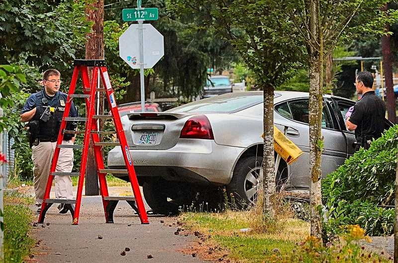 DAVID F. ASHTON - After turning the wrecked car upright, officers continue to look for evidence in the vehicle that sped away from the robbery, crashed and overturned.