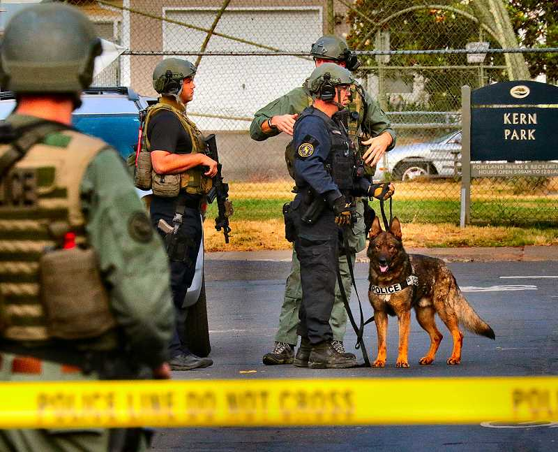 DAVID F. ASHTON - Near Kern Park, a PPB K9 team prepares to search for the armed robbery suspect.