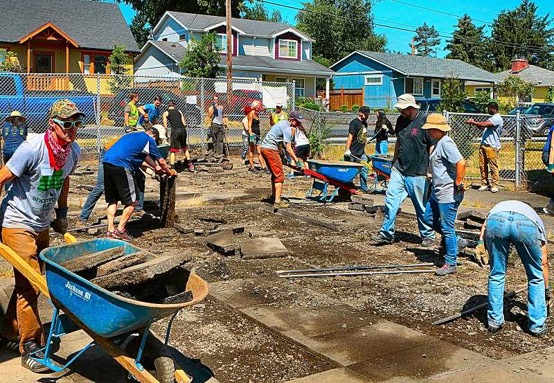 DAVID F. ASHTON - Dozens of volunteer show up at Woodmere Elementary School to de-pave an area that will become a natural play area and extension of their schools garden program.