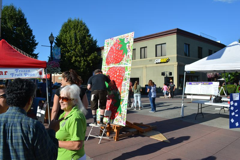 NEWS-TIMES/HILLSBORO TRIBUNE PHOTO: KATHY FULLER - Joshua Gundersen's strawberry painting is one of 10 panels that will become a mural. Linda Holland, in foreground, has organized local artists to paint the panels. Last summer she organized The Frida Project.