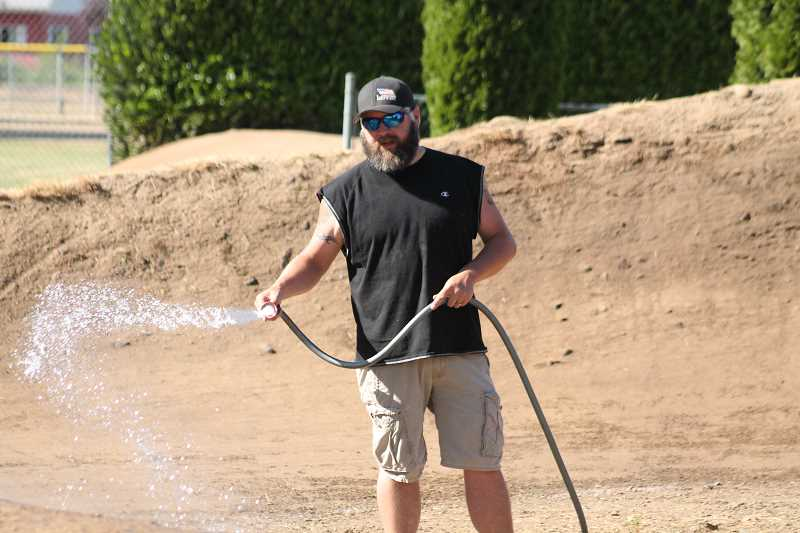 PIONEER PHOTO: CONNER WILLIAMS  - Mike Dahlberg waters down the dirt a few hours before a race on July 21. He has big plans for the track now that he's taken over as its operator, including a complete redesign, new starting gate, improved drainage system, and increased sponsorship.