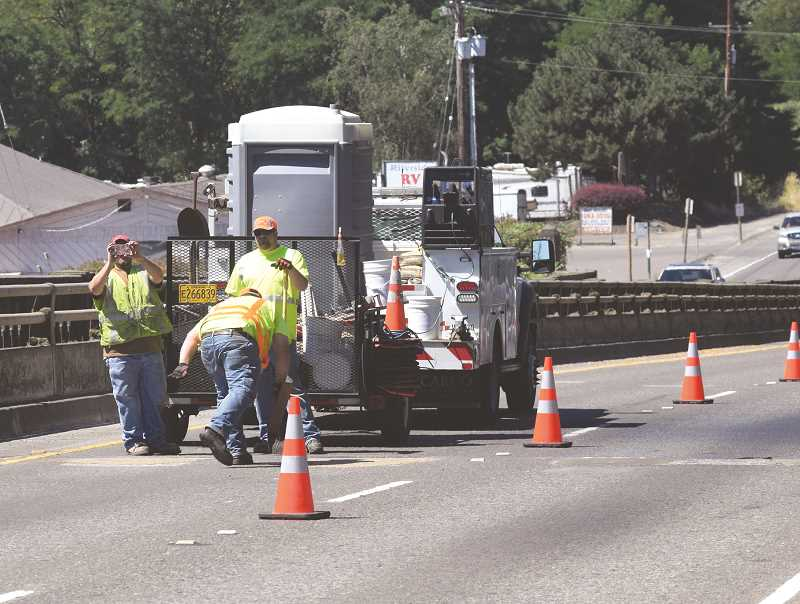 DANIEL PEARSON - As ODOT workers preapre the roadway for repair work on Friday, July 21, one worker takes a photo of a Canby Herald photoghper taking photos of them setting up.