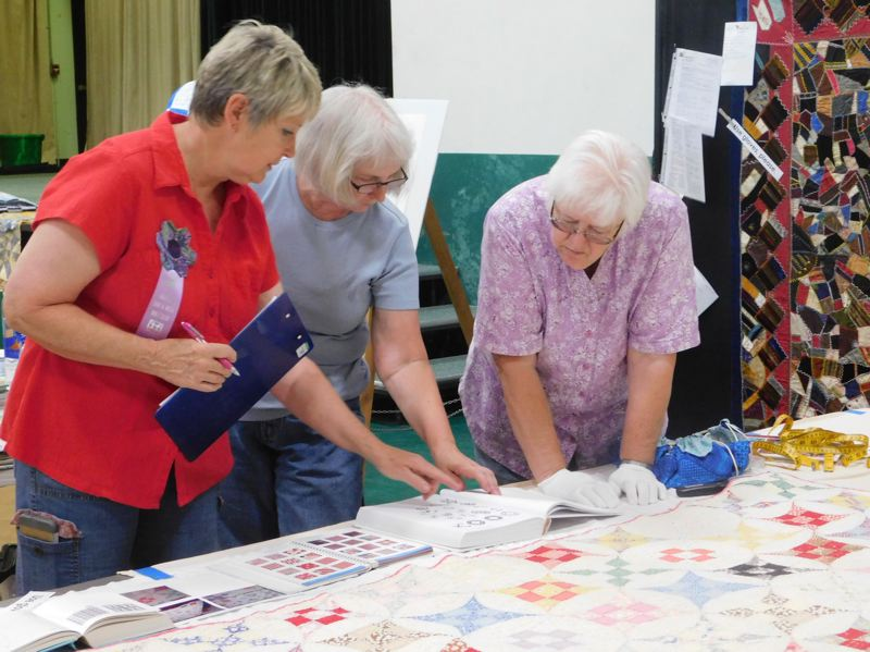 ESTACADA NEWS PHOTO: EMILY LINDSTRAND - The Garfield Skip-a-Week Clubs annual quilt show featured demonstrations of quilt documentations. Here, club members reference a book to help determine the age of a quilt.