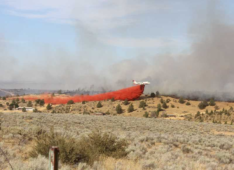 TONY AHERN/MADRAS PIONEER - A plane drops fire retandant between the fire and a home on the grassland, north of Madras.