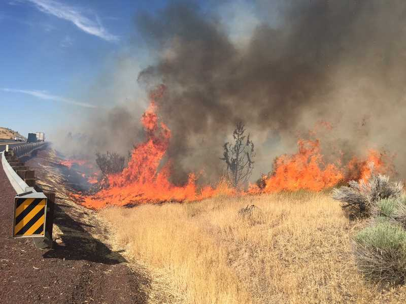 SUSAN MATHENY/MADRAS PIONEER - Wildfire flames whip around a corner next to U.S. Highway 97, north of Madras.