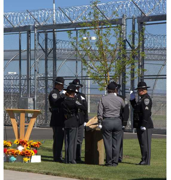 SUBMITTED PHOTO - Employees at Deer Ridge Correctional Institution, which recently celebrated its 10th anniversary, raised money for a memorial to recognize staff members who have passed away. During the July 11 ceremony, officials planted a crab apple blossom tree on the grounds to commemorate the officers.
