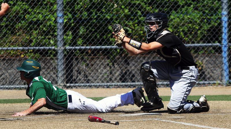 DAN BROOD - Sherwood catcher Ben Baxter (right) holds up the ball after tagging out West Linn's James Marshall at the plate during last week's OIBA tournament game, played at Wilsonville High School.