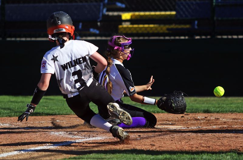 DAN BROOD - Tigard/TC's Hannah Wilken slides to home plate during the District 4 game with South Beaverton.